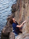 Flicka som upp klättrar en klippa arkivbild