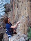 Flicka som upp klättrar en klippa royaltyfria foton