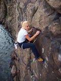 Flicka som upp klättrar en klippa royaltyfri foto