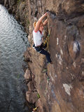 Flicka som upp klättrar en klippa arkivfoto