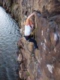 Flicka som upp klättrar en klippa arkivbilder