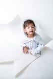 Flicka som ut får från ett hål på vit bakgrund #1 Royaltyfria Foton