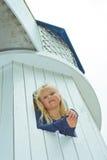 Flicka som ut ser fönstret av tornet Arkivbilder