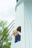 Flicka som ut ser fönstret av tornet Arkivbild