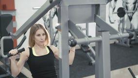 Flicka som utarbetar med simulatorn för muskler på armar och baksida i idrottshallen i 4k stock video