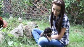 Flicka som utomhus kelar en valp i trädgården stock video