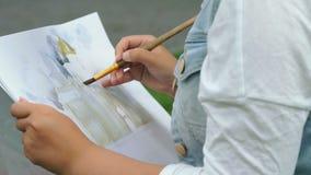 Flicka som utomhus målar en bild av det kyrkligt lager videofilmer