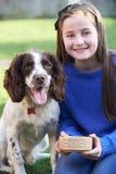 Flicka som utomhus matar den älsklings- spanielhunden från bunken i trädgård Arkivfoton