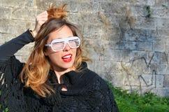 Flicka som utomhus poserar med stor partisolglasögon Royaltyfri Foto