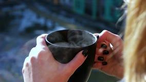 Flicka som utomhus rymmer en kopp av varmt te stock video
