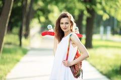 Flicka som utomhus rymmer ett plast- skridskobräde Arkivbild