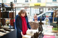Flicka som väljer en bok på parisisk loppmarknad Royaltyfria Bilder
