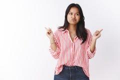 Flicka som vänder mot det invecklade beslutet som pekar grimcaing åt sidan som förvirras som att indikera högert och vänstert smi royaltyfri fotografi
