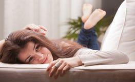 Flicka som väntar och drömmer på en soffa Arkivfoton