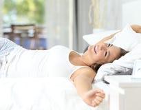 Flicka som vaknar sträcka upp armar på sängen Arkivbilder