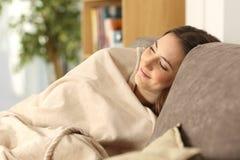 Flicka som varmt sover på en bekväm soffa arkivbild