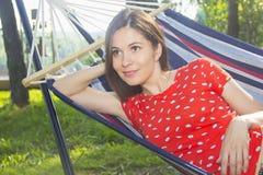 Flicka som vilar i natur i en hängmatta royaltyfria foton