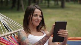 Flicka som vilar på en hängmatta med en minnestavla i hand på en skogbakgrund lager videofilmer