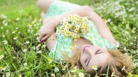 Flicka som vilar på naturen Härlig flicka som ligger på fältet lager videofilmer