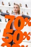 Flicka som visar procentsatsen av försäljningar på skodon Arkivfoto