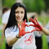 Flicka som visar röd hjärta Arkivfoton