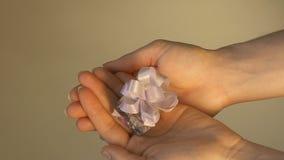 Flicka som visar upp en gåvaask i hennes händer, på en ljus bakgrund, slut, ultrarapid stock video