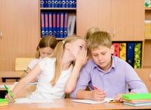 Flicka som viskar hemligheter av pojken i klassrumet Arkivfoto