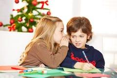 Flicka som viskar i öra av pojken på jul Arkivfoton