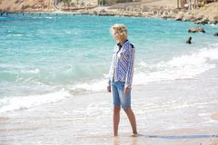 Flicka som wolking längs stranden Arkivbild