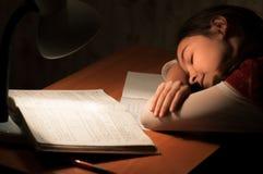 Flicka sovande på en bordlägga som gör läxa Royaltyfri Foto