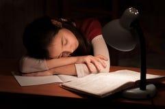 Flicka sovande på en bordlägga som gör läxa Arkivbild