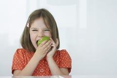 Flicka stickande gröna Apple Arkivbilder