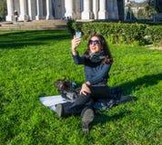 Flicka/student på en gräsmatta för grönt gräs som tar selfies Royaltyfria Foton