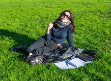 Flicka/student som dagdrömmer på en gräsmatta för grönt gräs Royaltyfri Foto