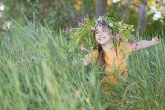 Flicka-tonåring i en krans från färger Arkivfoton