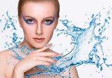 Flicka under färgstänk av vatten med ny hud arkivbilder