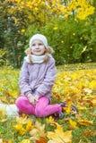 Flicka under fallande gula sidor Arkivbild