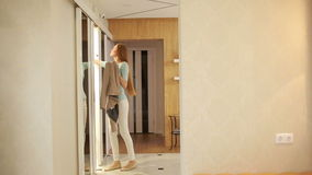 Flicka ut ur huset öppnar garderoben, tar påsen och omslaget lager videofilmer