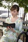 Flicka utomhus med bibeln Arkivfoton