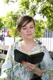 Flicka utomhus med bibeln Arkivbild