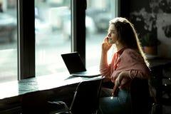 Flicka vid fönstret i ett kafé royaltyfri fotografi