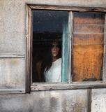 Flicka vid fönstret i ett trähus med dunkelt ljus royaltyfri fotografi