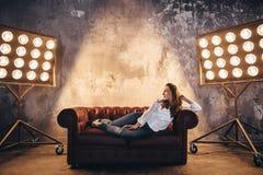 Flickaaktris på soffan i ljuset av soffits royaltyfri foto