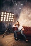 Flickaaktris på soffan i ljuset av soffits fotografering för bildbyråer
