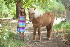 Flickaanseende med hennes gulliga isländska ponny Arkivfoton