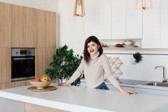Flickaanseende nära köksbordet Ljust vitt kök Lycklig le flicka i köket Kök Arkivfoton