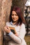 Flickaanseende och läsning en bok Royaltyfria Foton