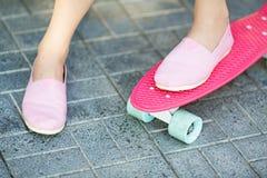 Flickaanseende på en rosa färgskateboard utomhus arkivfoton