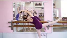 Flickaanseende på räcket i balettkorridor Ung ballerina som sträcker ut genom att använda balettbarren i studio Ung ballerina in stock video