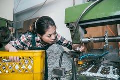 Flickaarbetare som arbetar i malning som bearbetar med maskin fabriken Royaltyfria Foton